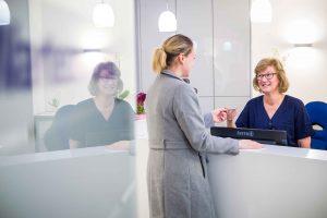 Eingangsbereich der Zahnarztpraxis. Frau Hollweck begrueßt Patientin